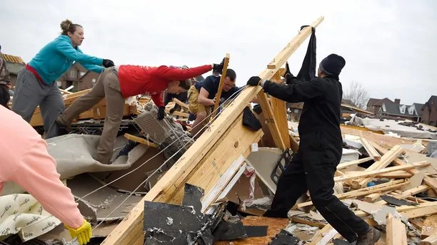 Neighbors help collect clothing and look for pets at a destroyed home Sunday morning after a fierce storm hit Saturday, Feb. 24, 2018, in the Farmington subdivision in Clarksville, Tenn. A strong storm system that included possible tornadoes roared eastward through the central United States, leaving demolished homes, damaged vehicles and uprooted trees in its wake.  (Lacy Atkins/The Tennessean via AP)