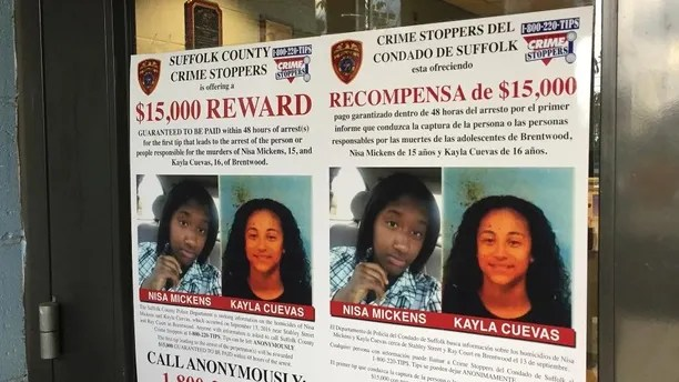 FILE - In this Oct. 24, 2016 file photo, a poster displayed at a Suffolk County police precinct in Bay Shore, N.Y., offers a $  15,000 reward for information leading to the arrest of the person(s) responsible for the slayings of Nisa Mickens and her lifelong friend Kayla Cuevas. Federal agents said Thursday March 2, 2017, that they have caught the members of a violent El Salvadoran street gang who killed three teenagers last year, including the two girls who were inseparable best friends at their Long Island high school. (AP Photo/Michael Balsamo, File)
