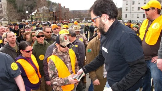 Rob Curtis, executive editor of a firearms magazine, hands out 30-round magazines at a gun rights event outside the Vermont State House in Montpelier on Saturday.