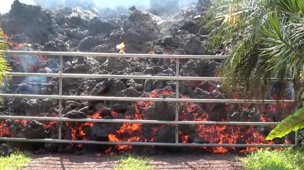 Lava advances towards a metal barrier in Puna, Hawaii, U.S., May 6, 2018 in this still image obtained from social media video. WXCHASING via REUTERS ATTENTION EDITORS - THIS IMAGE WAS PROVIDED BY A THIRD PARTY. NO RESALES. NO ARCHIVES. MANDATORY CREDIT: WXCHASING. NO NEW USES AFTER JUNE 5, 2018. UNITED STATES OUT. - RC1F425BA840