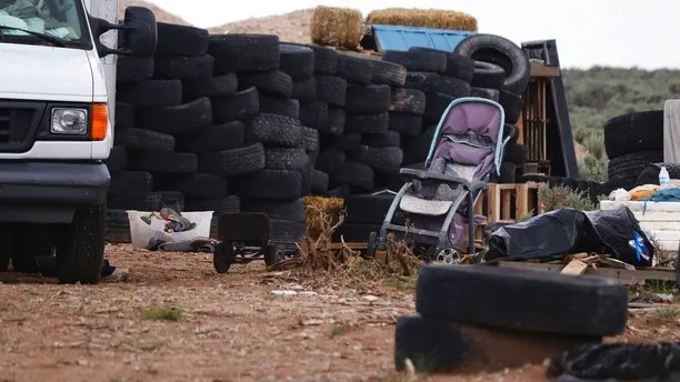 This Aug. 5, 2018 photo shows debris outside the location where people camped near Amalia, N.M. Three women believed to be the mothers of 11 children found hungry and living in a filthy makeshift compound in rural northern New Mexico have been arrested, following the weekend arrests of two men, authorities said Monday, Aug. 6. (Jesse Moya/The Taos News via AP)