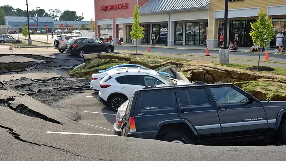 Vehicles sit at the bottom of a sinkhole that opened Friday in a parking lot at the Tanger Outlets shopping center in Lancaster, Pennsylvania.