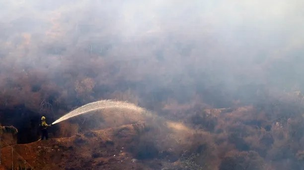 A firefighter hoses down hot spots caused by a wildfire Friday, Aug. 10, 2018, in Lake Elsinore, Calif. (AP Photo/Marcio Jose Sanchez)