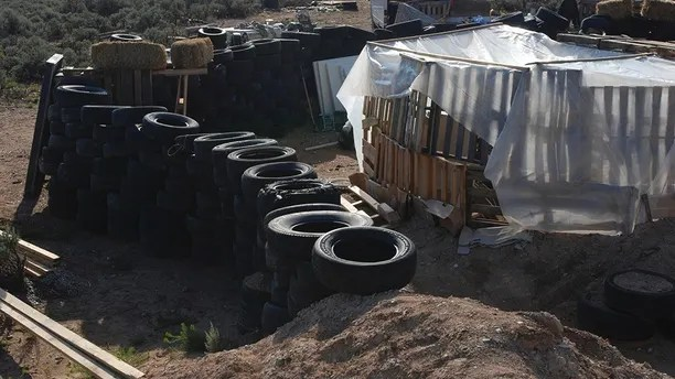 Tires form a wall at a squalid makeshift living compound in Amalia, N.M., on Friday, Aug. 10, 2018, where five adults were arrested on child abuse charges and remains of a boy were found. The remains, which haven't been positively identified, may resolve the fate of Abdul-ghani Wahhaj, a missing, severely disabled Georgia boy. Eleven other children were found at the compound during a raid last week.  (AP Photo/Morgan Lee)