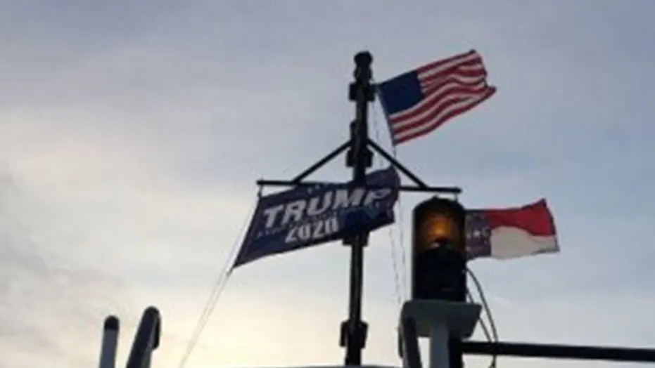 """Two North Carolina state workers were suspended for a week without pay after flying a large """"Trump 2020"""" flag atop an Outer Banks ferry in July."""