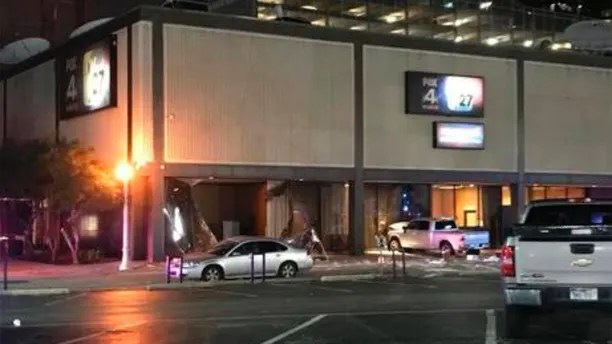 This image taken from video by KDFW Fox 4 shows a pickup truck after a man crashed the vehicle into the side of the Fox affiliate television station building in downtown Dallas on Wednesday, Sept. 5, 2018. The man was arrested after pacing and scattering papers outside. Despite the crash, nobody was hurt. (KDFW Fox 4 via AP)