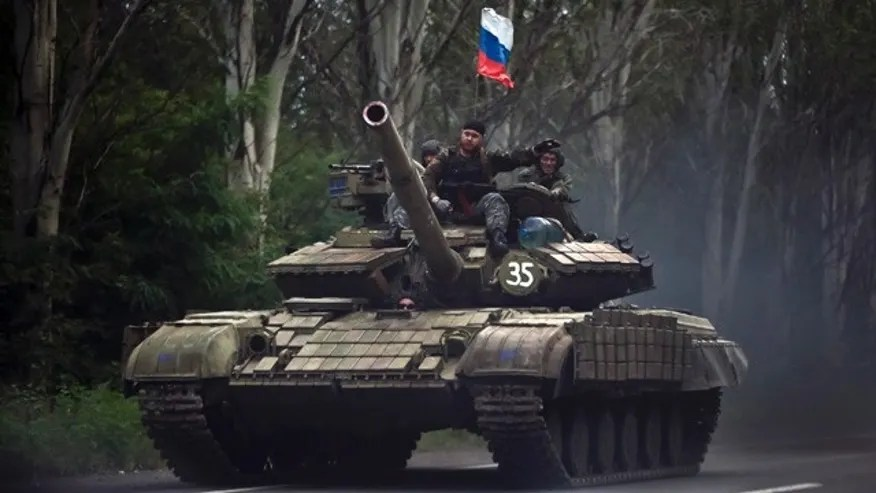 FILE - In this Sunday, July  29, 2015, file photo, pro-Russian rebels ride on a tank flying Russia's flag on a road east of Donetsk, eastern Ukraine. (AP Photo/Vadim Ghirda, File)