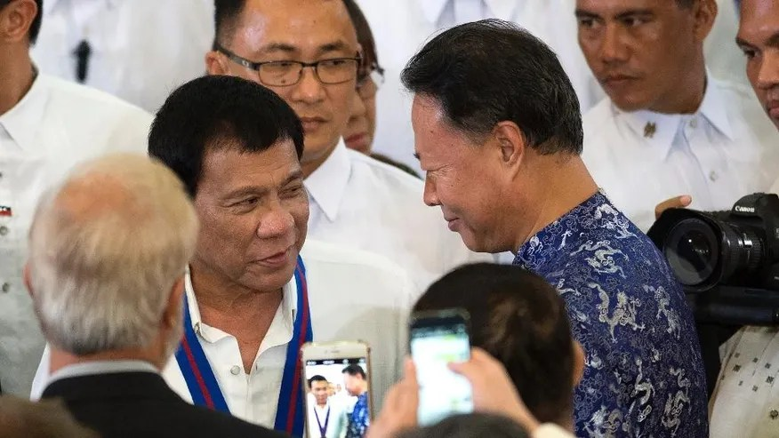 FILE - In this Wednesday, Aug. 17, 2016 file photo, Philippine President Rodrigo Duterte, left, talks with Chinese Ambassador to the Philippines Zhao Jianhua, right, during the 115th Police Service Anniversary at the Philippine National Police (PNP) headquarters in Manila. Duterte said last week that he would not raise maritime disputes with China at a meeting of Southeast Asian nations in Laos next month, preferring to talk quietly with Chinese officials. (Noel Celis/Pool Photo via AP, File)