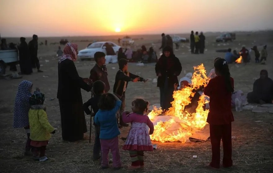 In this Thursday, Nov. 17, 2016 photo, Iraqis, who fled the fighting between Iraqi forces and Islamic State militants, gather around flames to warm themselves from the cold, as they wait to cross to the Kurdish controlled area, in the Nineveh plain, northeast of Mosul. Cloudy skies neutralized air power in Mosul on Thursday, Iraqi forces said, hampering their advance into the northern city, although they still faced deadly attacks by Islamic State militants that killed seven civilians and two soldiers. (AP Photo/Hussein Malla)