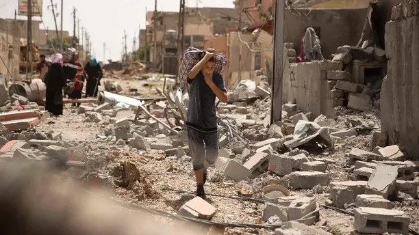 An Iraqi boy carries heavy belongings through rubble as he flees fighting between Iraqi special forces and Islamic State militants, in western Mosul, Iraq, Monday, May 15, 2017. (AP Photo/Maya Alleruzzo)