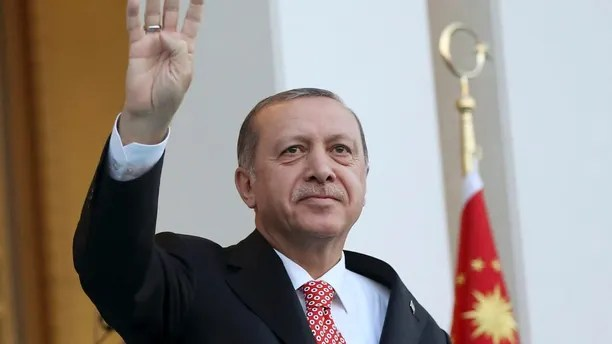 Turkey's President Recep Tayyip Erdogan waves to supporters outside the Presidential Palace, during the inauguration of a monument to commemorate the victims of the July 15, 2016 failed coup attempt, early Sunday, July 16, 2017 in Ankara, Turkey. Turkey marked the anniversary of the country's crushed military coup with a series of rallies and other commemorative events. (Presidency Press Service via AP, Pool)