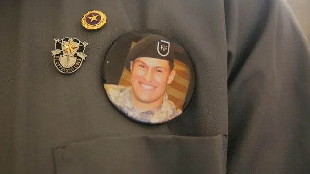 FILE - In this Monday, July 17, 2017, file photo, a badge with a photo of Sgt. Matthew Lewellen, a slain U.S. Army Green Beret, is shown pinned to the chest of his father, Charles, in Amman, Jordan, Monday, July 17, 2017. Jordan's military has released a security camera video of a shooting last year in which a Jordanian soldier killed three U.S. military trainers at the entrance to an air base in the kingdom. (AP Photo/Reem Saad, File)