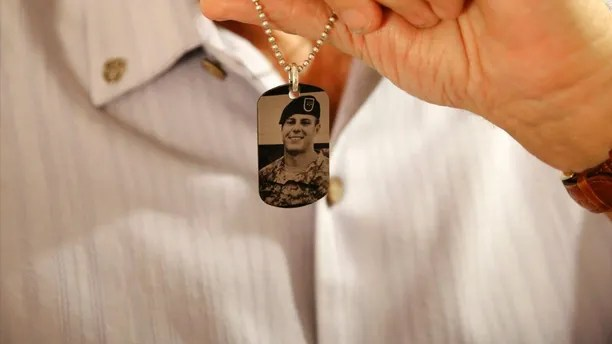 FILE -- In this June 17, 2017 file photo, Brian McEnroe, the father of fallen U.S. Green Beret Kevin McEnroe, displays a memorial dog tag depicting his fallen son, in Amman, Jordan. First Sgt. Marik al-Tuwayha, the Jordanian soldier charged with killing three U.S. Army Green Berets including McEnroe, in November 2016, told a military court Tuesday, July 4, 2017, that he opened fire because he thought fellow Jordanian troops had come under attack. Al-Tuwayha said he felt no resentment toward Americans and that he had joked and chatted with the U.S. trainers before the incident. (AP Photo/Sam McNeil)