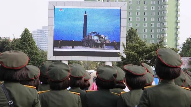 People fill the square of the main railway station to watch a televised news broadcast of the test-fire of an inter-continental ballistic rocket Hwasong-12, Wednesday, August 30, 2017, in Pyongyang, North Korea. By firing a missile over Japan and putting the Asia-Pacific, including U.S. territory Guam, on notice for more and more ambitious tests, the North has won itself greater space for more weapons tests Washington and Seoul see as provocative.  (AP Photo/Kim Kwang Hyon)
