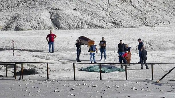 The coffins of three people who died when they fell into a crater in a steamy volcanic field in Pozzuoli, near Naples, Italy, are carried away Tuesday, Sept. 12, 2017. Italian news reports say an 11-year-old Italian boy and his parents died in a steamy volcanic field near Naples. ANSA said the parents tried to rescue the boy after he entered an off-limits area at the Solfatara Crater in Pozzuoli, and was overcome by gases, losing consciousness. (Ciro Fusco/ANSA via AP)