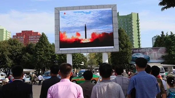 "People watch a launching of a Hwasong-12 strategic ballistic rocket aired on a public TV screen at the Pyongyang Train Station in Pyongyang, North Korea, Saturday, Sept. 16, 2017. North Korean leader Kim Jong Un said his country is nearing its goal of ""equilibrium"" in military force with the United States, as the United Nations Security Council strongly condemned the North's ""highly provocative"" ballistic missile launch over Japan on Friday. (AP Photo/Jon Chol Jin)"