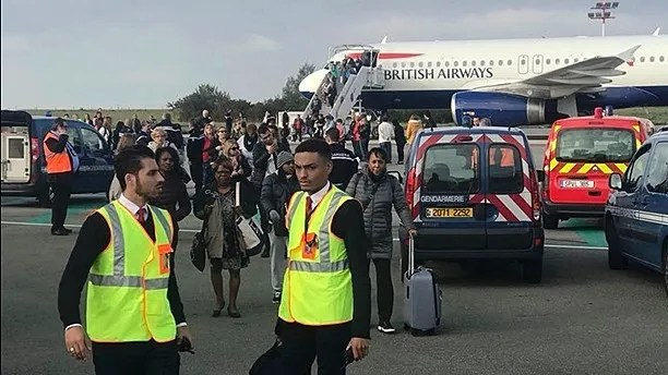 In this photo provided by James Anderson, people are evacuated from a British Airways plane, on the tarmac of Charles de Gaulle airport, in Paris, Sunday, Sept. 17, 2017.  Police and firefighters checked a British Airways plane on the tarmac of Paris' Charles de Gaulle airport Sunday morning after reports of a security threat but authorities determined it was a false alarm. James Anderson, a 20-year-old entrepreneur on the flight from Paris to London's Heathrow Airport, told The Associated Press that the pilot initially told passengers there were technical issues. ( James Anderson via AP)