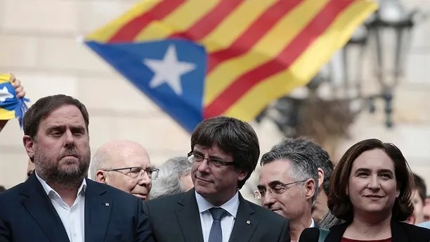 From left to right: Catalan regional Vice-President Oriol Junqueras, Catalan President Carles Puigdemont and Barcelona's mayor Ada Colau stands outside during a protest called by pro-independence at the Palau Generalitat in Barcelona, Spain, Monday, Oct. 2, 2017. Catalonia's government will hold a closed-door Cabinet meeting Monday to discuss the next steps in its plan to declare independence from Spain following a disputed referendum marred by violence. (AP Photo/Manu Fernandez)