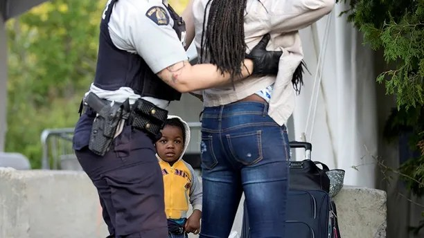 Two-year-old Evanston, whose family stated they are from Haiti, watches as a Royal Canadian Mounted Police (RCMP) officer pats down his mother after they crossed the US-Canada border from Champlain, New York into Lacolle, Canada August 11, 2017. REUTERS/Christinne Muschi     TPX IMAGES OF THE DAY - RC17F4D8DE90