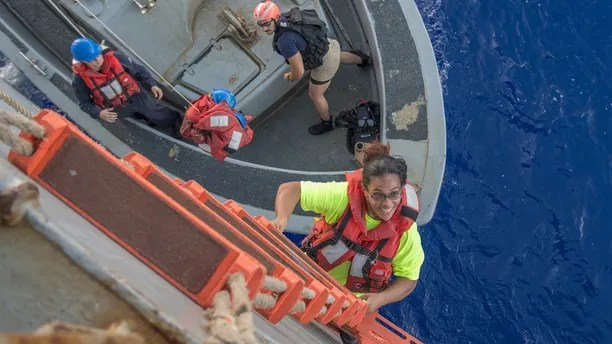 171025-N-UX013-177 PACIFIC OCEAN (Oct. 25, 2017) Tasha Fuiaba, an American mariner who had been sailing for five months on a damaged sailboat, climbs the accommodation ladder to board the amphibious dock landing ship USS Ashland (LSD 48). Ashland, operating in the Indo-Asia-Pacific region on a routine deployment, rescued two American mariners who had been in distress for several months after their sailboat had a motor failure and had strayed well off its original course while traversing the Pacific Ocean. (U.S. Navy photo by Mass Communication Specialist 3rd Class Jonathan Clay/Released)