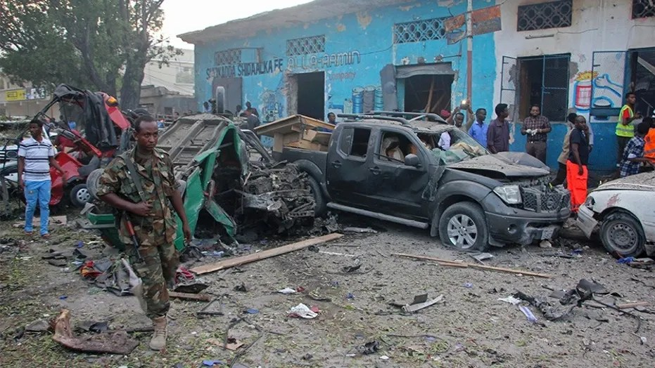 Somali soldier walk near wreckage of vehicles after a car bomb was detonated in Mogadishu, Somalia, Saturday.