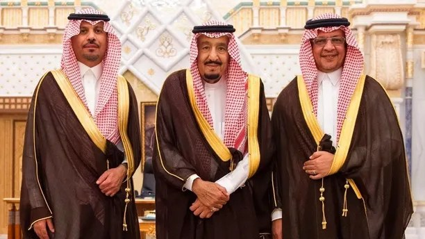 In this photo provided by the Saudi Press Agency, the new Economy and Planning Minister, Mohammad al-Tuwaijri, right and the new National Guard chief, Prince Khalid bin Ayyaf al-Muqrin, left, pose for a photo with King Salman during a swearing in ceremony, in Riyadh, Saudi Arabia, Monday, Nov. 6, 2017. The king has sworn in new officials to take over from a powerful prince and former minister believed to be detained in a large-scale sweep that has shocked the country and upended longstanding traditions within the ruling family. (Saudi Press Agency, via AP)