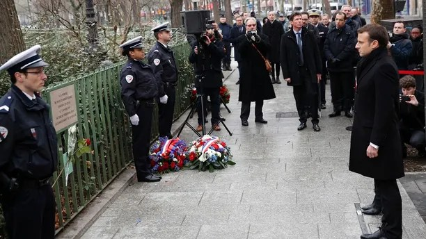 French President Emmanuel Macron observes a minute of silence in front of the plaque commemorating late police officer Ahmed Merabet to mark the third anniversary of the attack, in Paris, Sunday, Jan. 7, 2018. Macron paid respects to the 17 people killed when Islamic extremists attacked satirical newspaper Charlie Hebdo and a kosher supermarket three years ago, in the first of several attacks to rock France. (AP Photo/Christophe Ena, Pool)