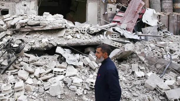 A man is seen near a damaged building in the besieged town of Douma, Eastern Ghouta, Damascus, Syria February 25, 2018. REUTERS/Bassam Khabieh - RC15B578C0D0