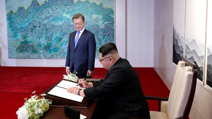 South Korean President Moon Jae-in watches as North Korean leader Kim Jong Un writes in a guestbook at the Peace House at the truce village of Panmunjom inside the demilitarized zone separating the two Koreas, South Korea, April 27, 2018.