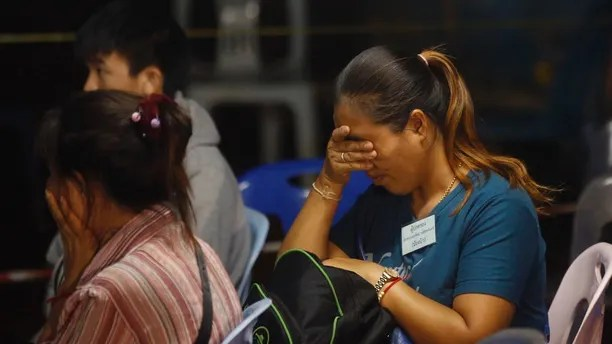 Family members react after hearing the news that the missing 12 boys and their soccer coach have been found, in Mae Sai, Chiang Rai province, in northern Thailand, Monday, July 2, 2018. A Thai provincial governor says all 12 boys and their coach have been found alive in the cave where they went missing over a week ago in northern Thailand. (AP Photo/Sakchai Lalit)