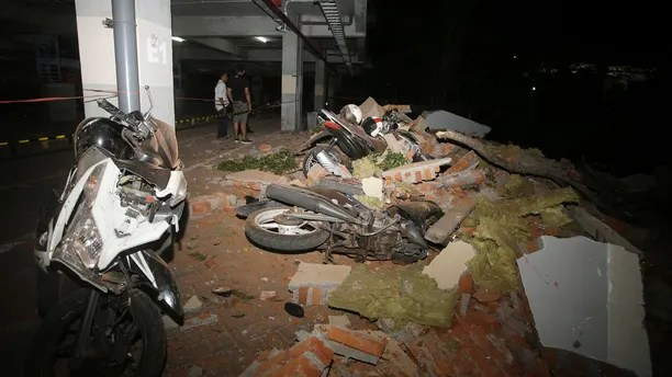 Debris on top of a motorcycles after an earthquake in Bali, Indonesia, Sunday, Aug. 5, 2018. A strong earthquake struck the Indonesian tourist island of Lombok on Sunday, killing at least three people and shaking neighboring Bali, one week after another quake on Lombok killed more than a dozen. (AP Photo/Firdia Lisnawati)