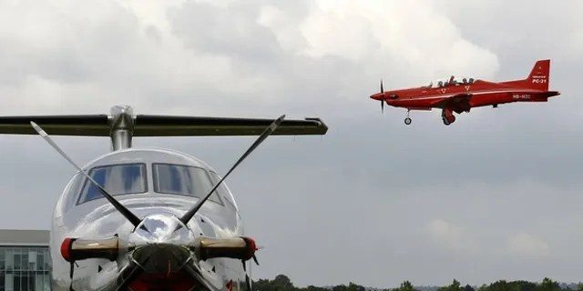Pilatus DC-21 (R) comes into land over a Pilatus PC-12.