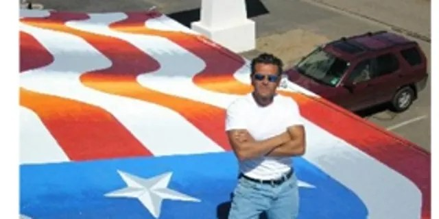 Artist Scott LoBaido showcasing his flag painting on a rooftop in Pioria, Ariz.