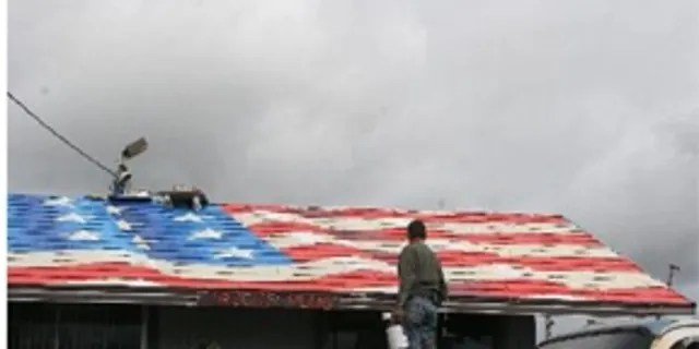 Artist Scott LoBaido's flag painting on a rooftop in Everett, Wash.