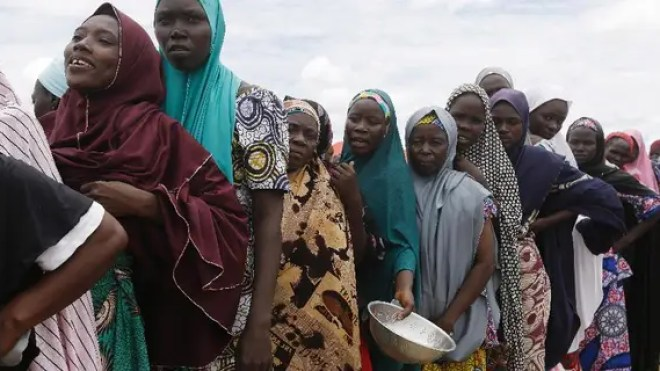 FILE-In this file photo taken Saturday, Aug. 27, 2016, women displaced by Islamist extremists wait for food to be handed out to them at the Bakassi camp in Maiduguri, Nigeria. Many say the dangerous journey is preferable to the hunger, humiliation and inhumane conditions in refugee camps where more than 1 million Nigerians, displaced by Boko Haram, are waiting to go home.