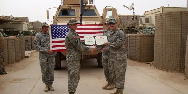 Army 1st Lt. Michael Behenna, at left in front of the American flag, pictured in Iraq with some members of his platoon. In the back right holding the flag is Adam Kohlhaas, who was killed in a roadside bombing tied to an Al Qaeda cell.