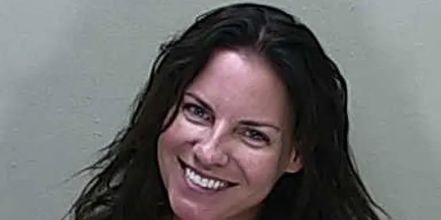 Angenette Welk, 44, smiling in her mugshot following her arrest in a DUI crash that killed a 60-year-old woman.