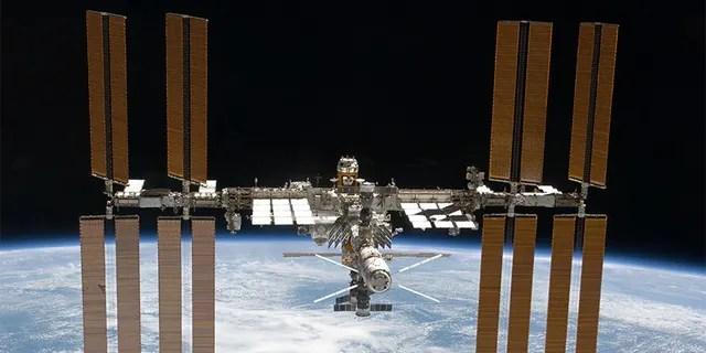 La station spatiale internationale est représentée sur cette image photographiée par un membre d'équipage de la STS-133 dans la navette Discovery après que la station et la navette ont commencé leur séparation relative après le désamarrage