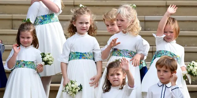 Bridesmaids and page boys, including Prince George, center, and Princess Charlotte, left, wave as they leave after the wedding ceremony of Princess Eugenie of York and Jack Brooksbank. (AP)