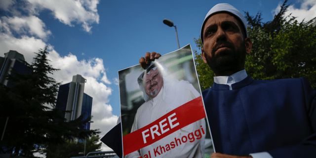 Holding a poster of missing Saudi writer Jamal Khashoggi, a man stands near the Saudi Arabia consulate in Istanbul, Friday, Oct. 5, 2018. Khashoggi, a 59-year-old veteran journalist who has lived in self-imposed exile in the U.S. since Prince Mohammed's rise to power, disappeared Oct. 2 while on a visit to the consulate to get paperwork done to be married to his Turkish fiancée. The Saudi Consulate insists Khashoggi left its building, contradicting Turkish officials who say they believe he is still there. (AP Photo/Emrah Gurel)