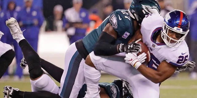 New York Giants running back Saquon Barkley (26) is tackled by Philadelphia Eagles' Malcolm Jenkins (27) during the first half of an NFL football game in East Rutherford, N.J., Oct. 11, 2018.