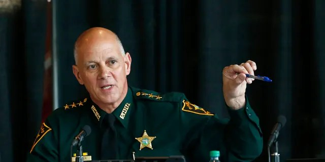 In this June 7, 2018 file photo Marjory Stoneman Douglas High School Public Safety Commission chair and Pinellas County Sheriff Bob Gualtieri gestures as he speaks during a commission meeting in Sunrise, Fla. Guiltieri says he now believes trained, volunteer teachers should have access to guns so they can stop shooters who get past other safeguards.