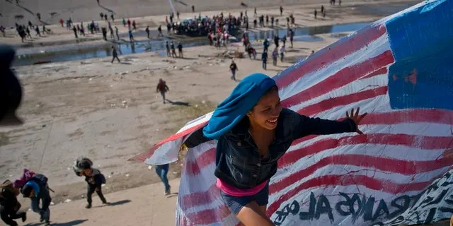 Migrants cross a riverbed at the Mexico-U.S. border after getting past a line of police at the Chaparral border crossing in Tijuana, Mexico, Sunday, Nov. 25, 2018, as they try to reach the U.S. The mayor of Tijuana has declared a humanitarian crisis in his border city and says that he has asked the United Nations for aid to deal with the approximately 5,000 Central American migrants who have arrived in the city. (AP Photo/Ramon Espinosa)