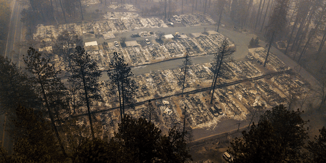 FILE - In this Nov. 15, 2018, file photo, residences leveled by a wildfire line a neighborhood in Paradise, Calif. Mass shootings, hurricanes, fires - for many people across the nation, 2018 was a year of loss unlike any other. As the quintessentially American holiday of Thanksgiving approaches, some will abandon traditions or chose not to mark the holiday at all. Others will celebrate new friendships forged in the wake of tragedy. (AP Photo/Noah Berger, File)
