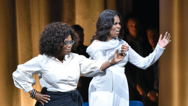 """Michelle Obama, right, is greeted by Oprah Winfrey to discusses her new book during an intimate conversation to promote """"Becoming"""" at the United Center on Tuesday, Nov. 13, 2018, in Chicago. (Photo by Rob Grabowski/Invision/AP)"""