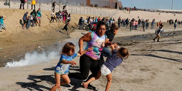 A migrant family, part of a caravan of thousands traveling from Central America en route to the United States, run away from tear gas in front of the border wall between the U.S and Mexico in Tijuana, Mexico November 25, 2018. REUTERS/Kim Kyung-Hoon - RC1CEA31D520