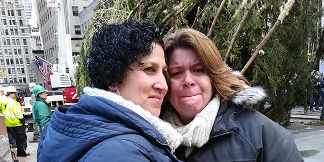 Lissette Gutierrez, left, hugs her wife, Shirley Figueroa, with the 72-foot-tall Norway spruce that the couple donated in the background, Saturday, Nov. 10, 2018 in New York. The tree was hoisted into position by crane after making the 60-mile trip from the couple's Wallkill, New York, home and will become the 2018 Rockefeller Center Christmas tree. (AP Photo/Julie Walker)