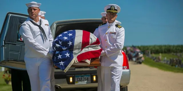 FILE - In this July 7, 2018 file photo, U.S. Navy sailors remove the casket with the remains of Seaman First Class Leon Arickx from a hearse at Sacred Heart Cemetery in Osage, Iowa. Arickx' remains, which were unidentifiable after his death after the Japanese attack at Pearl Harbor in 1941, were identified through DNA testing earlier this year. (Chris Zoeller/Globe-Gazette via AP, File)
