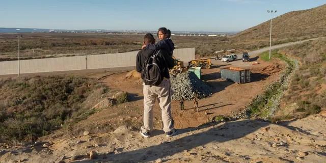 Un inmigrante de Honduras sostiene a su hija mientras los oficiales de la Patrulla Fronteriza los miran antes de saltar la cerca de la frontera para ingresar al lado estadounidense a San Diego, California, desde Tijuana, México, el jueves 3 de enero de 2019. Desanimado por el largo tiempo. a la espera de solicitar asilo a través de los puertos de entrada oficiales, muchos inmigrantes de caravanas recientes están eligiendo cruzar el muro fronterizo de los EE. UU. y entregarse a los agentes de la patrulla fronteriza. (Foto AP / Daniel Ochoa de Olza)