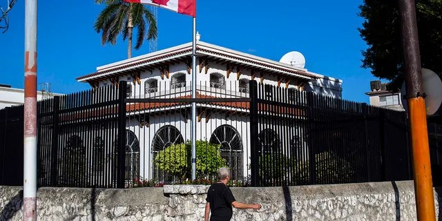 In this April 17, 2018 file photo, a man walks beside Canada's embassy in Havana, Cuba. Canada announced Wednesday, Jan. 30, 2019, it is removing up to half of the Canadians at its embassy in Cuba after another diplomat was found to have fallen mysteriously ill.